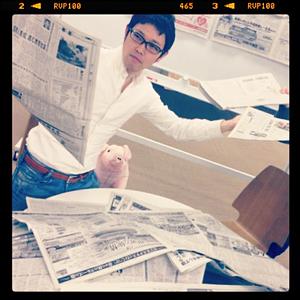 大量の新聞を机に広げて読むニュース推薦職人
